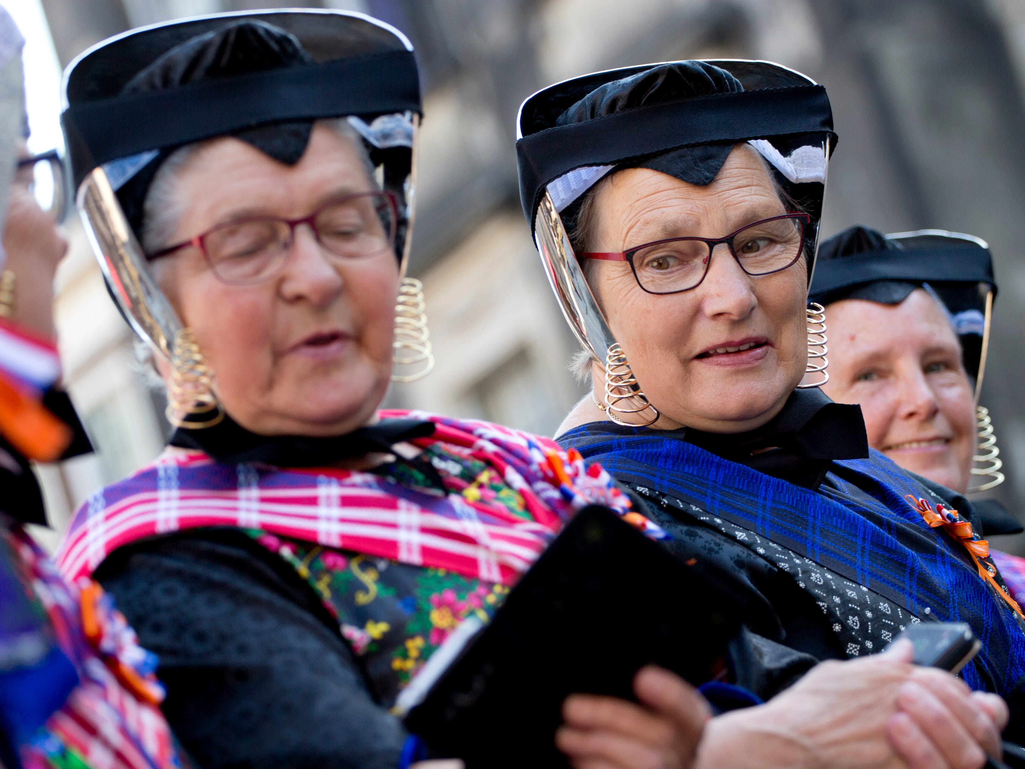 Woman in traditional Dutch clothing from the village of Staphorst look at their smart phones as they wait for Dutch King Willem-Alexander and Queen Maxima's arrival in a horse-drawn carriage at the Knight's Hall in The Hague, Netherlands, Tuesday, Sept. 18, 2018, for a ceremony marking the opening of the parliamentary year with a speech by King Willem-Alexander outlining the government's budget plans for the year ahead.