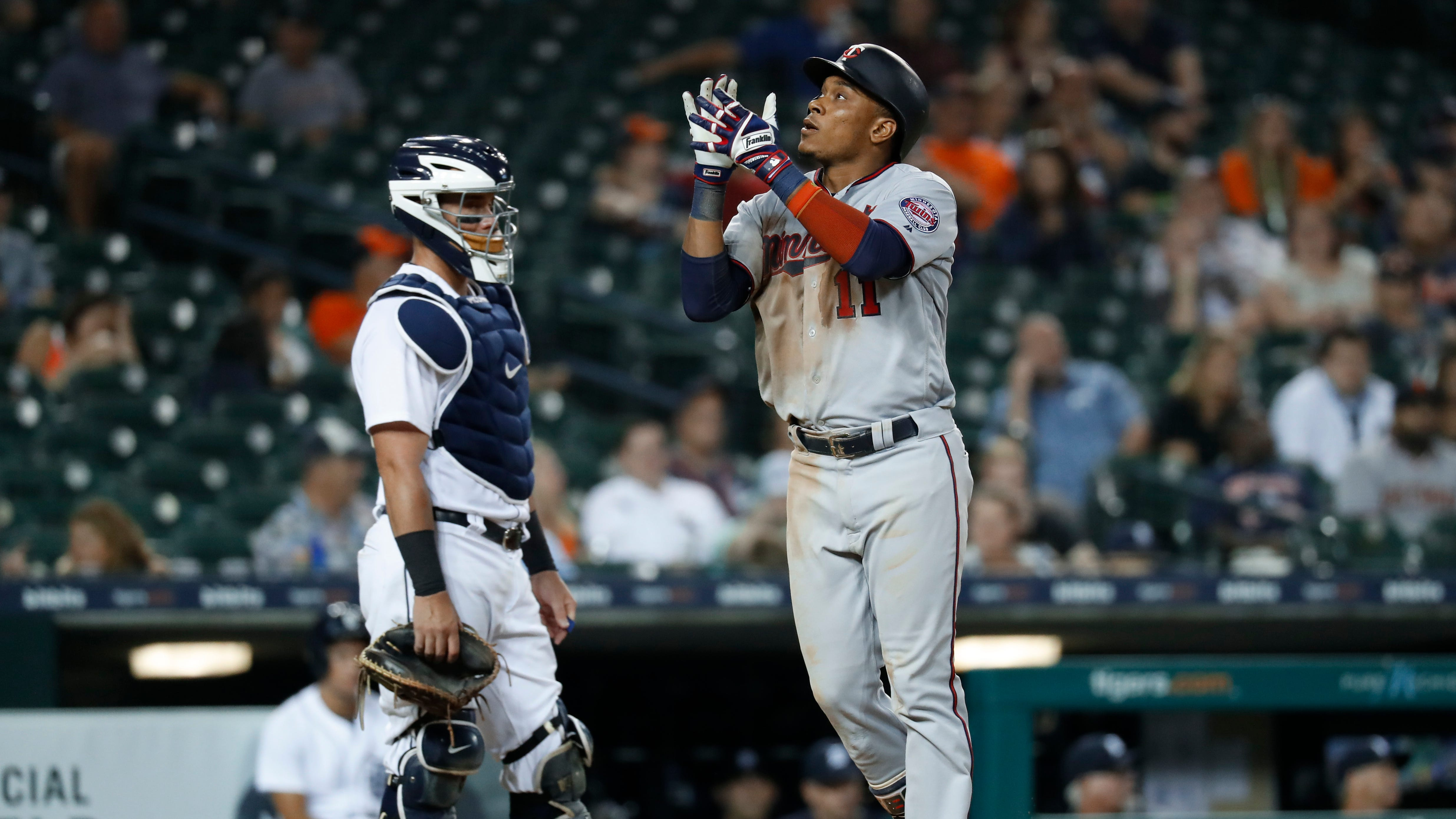 The Minnesota Twins' Jorge Polanco  celebrates his solo home run in the ninth inning in front of Detroit Tigers catcher James McCann.