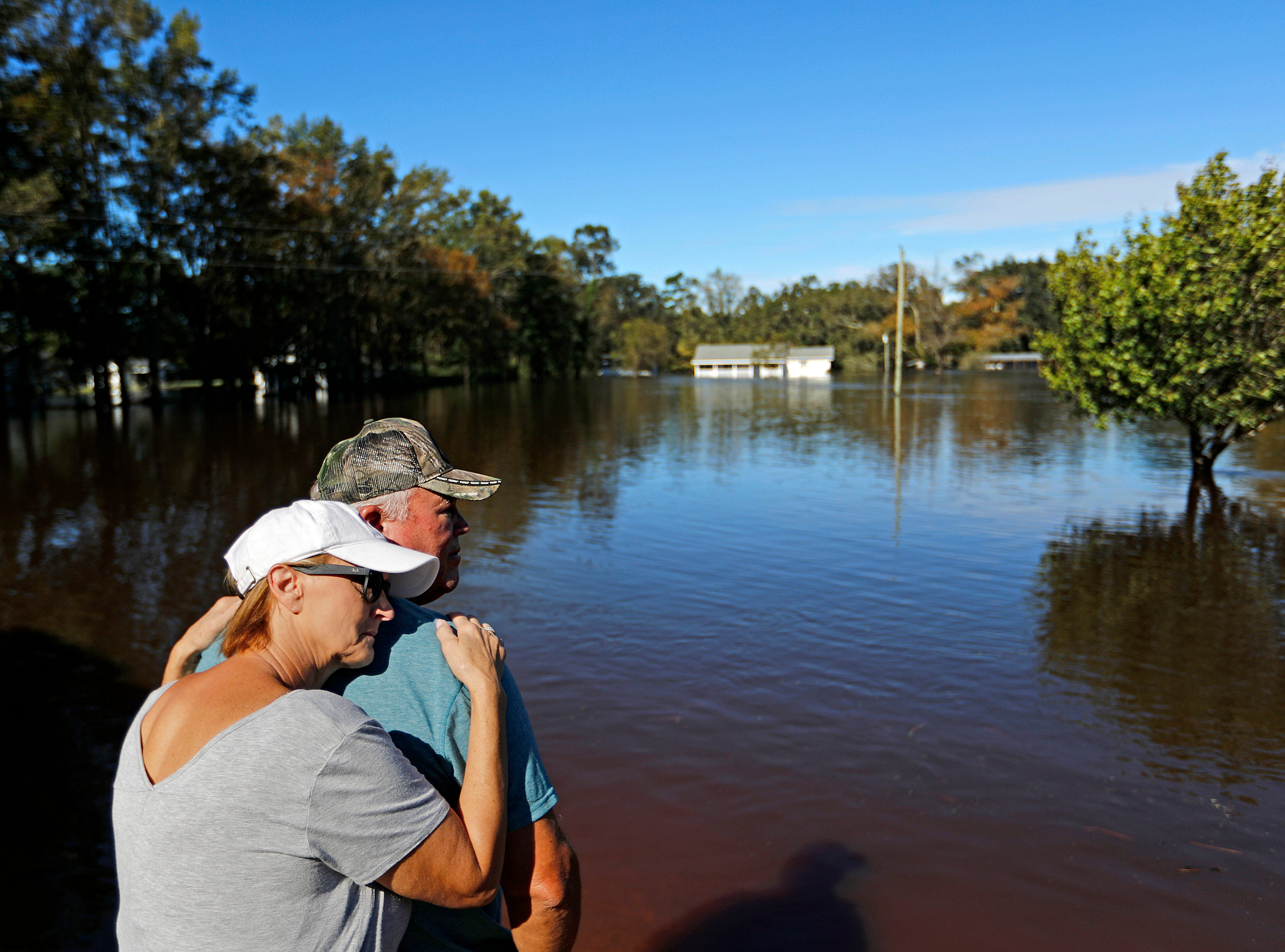 "Dianna Wood, embraces her husband Lynn, as they look out over their flooded property as the Little River continues to rise in the aftermath of Hurricane Florence in Linden, N.C., Tuesday, Sept. 18, 2018. ""I'm still hopeful,"" said Lynn about his home which currently has water up to the front step. ""In another foot, I'll be heartbroken,"" he added."