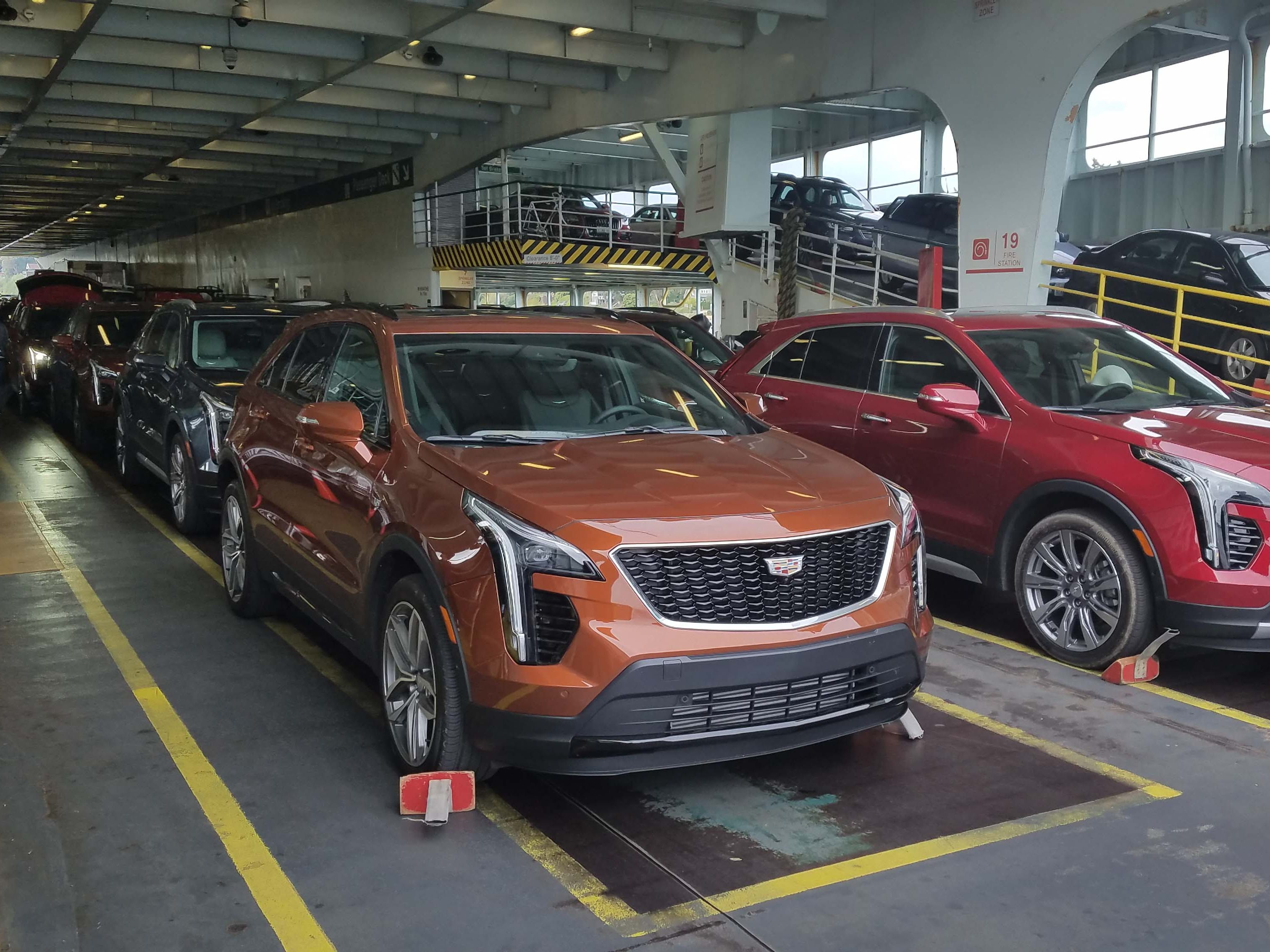 A fleet of brand-new, 2019 Cadillac XT4 utes crosses Seattle's Puget Sound on a ferry. The new car has a presence that other entry-level Caddies have lacked.