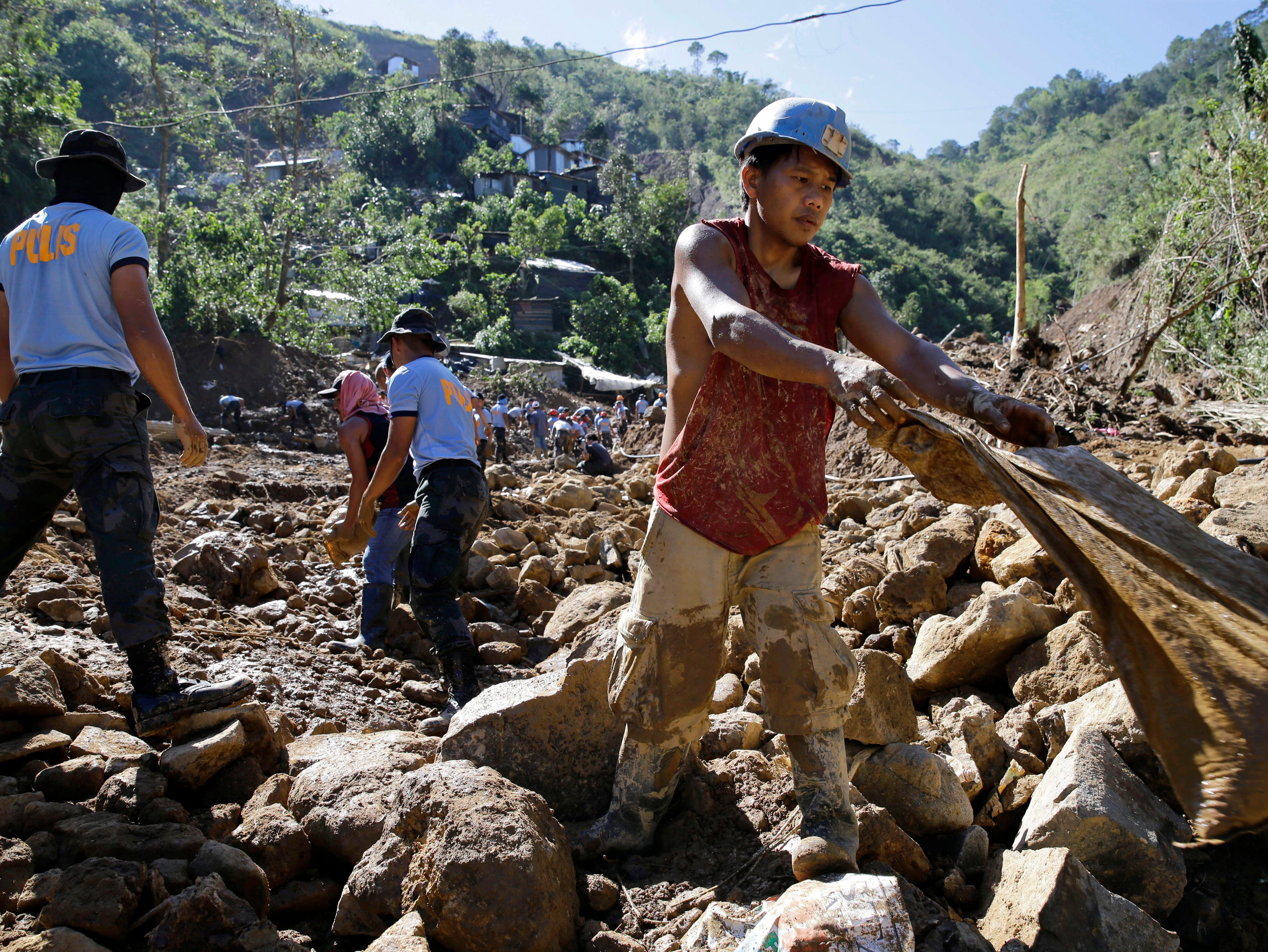 A Filipino miner, right, joins search operations at the site where victims are believed to have been buried by a landslide triggered by Typhoon Mangkhut as it lashed across Itogon, Benguet province, northern Philippines, Tuesday, Sept. 18, 2018.