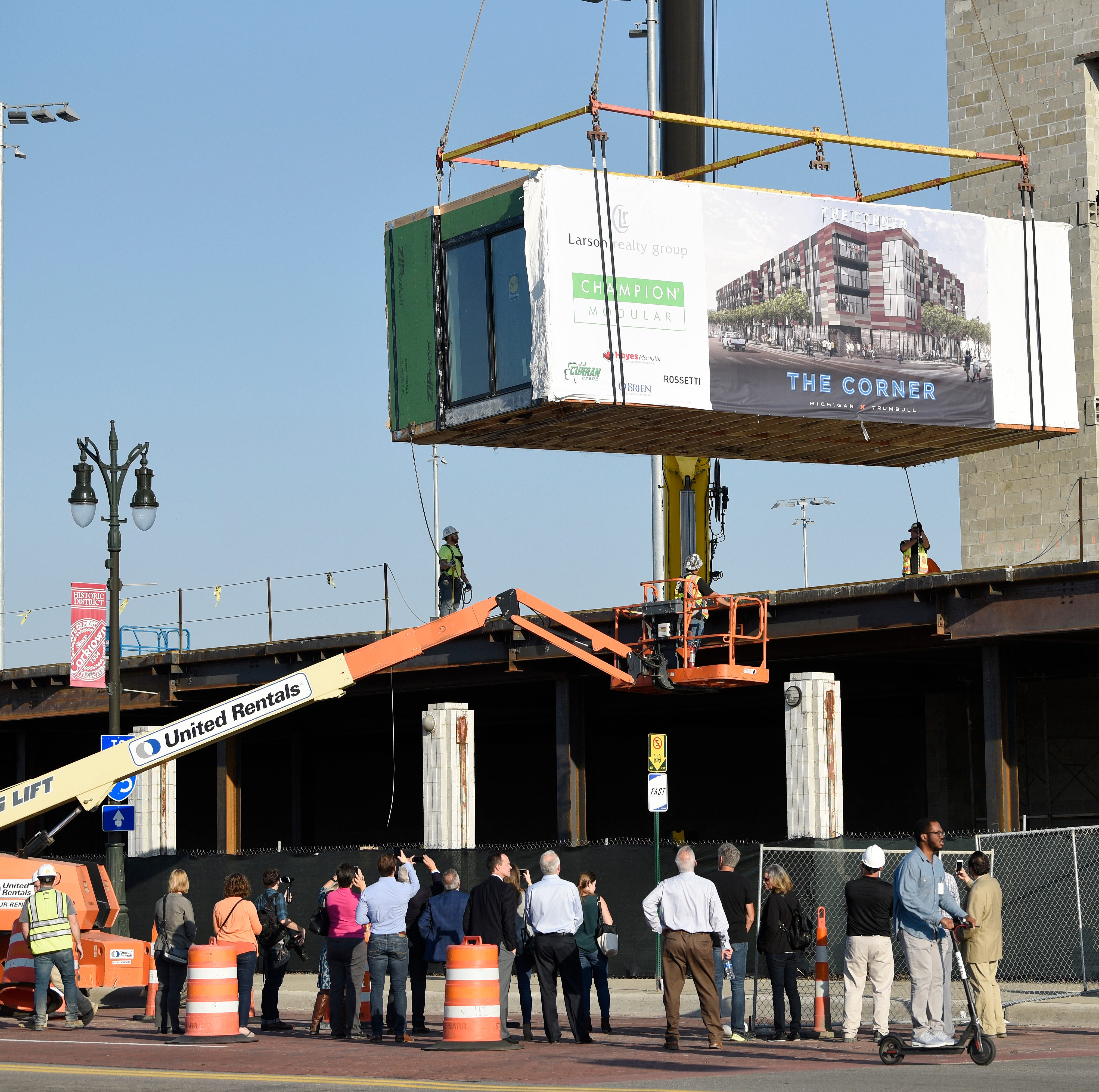 A crowd watches as a modular apartement unit is installed on the first floor podium of the 'Corner' a $30 million mixed-use development project at the corner of Michigan Ave. and Trumbull St on the former Tiger Stadium site in Detroit on Tuesday, September 18, 2018.