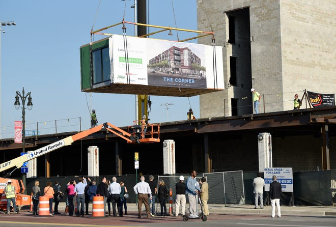 "A crowd watches as a modular unit is installed at ""The Corner,"" a $30 million mixed-use development project at the corner of Michigan and Trumbull, on Tuesday."