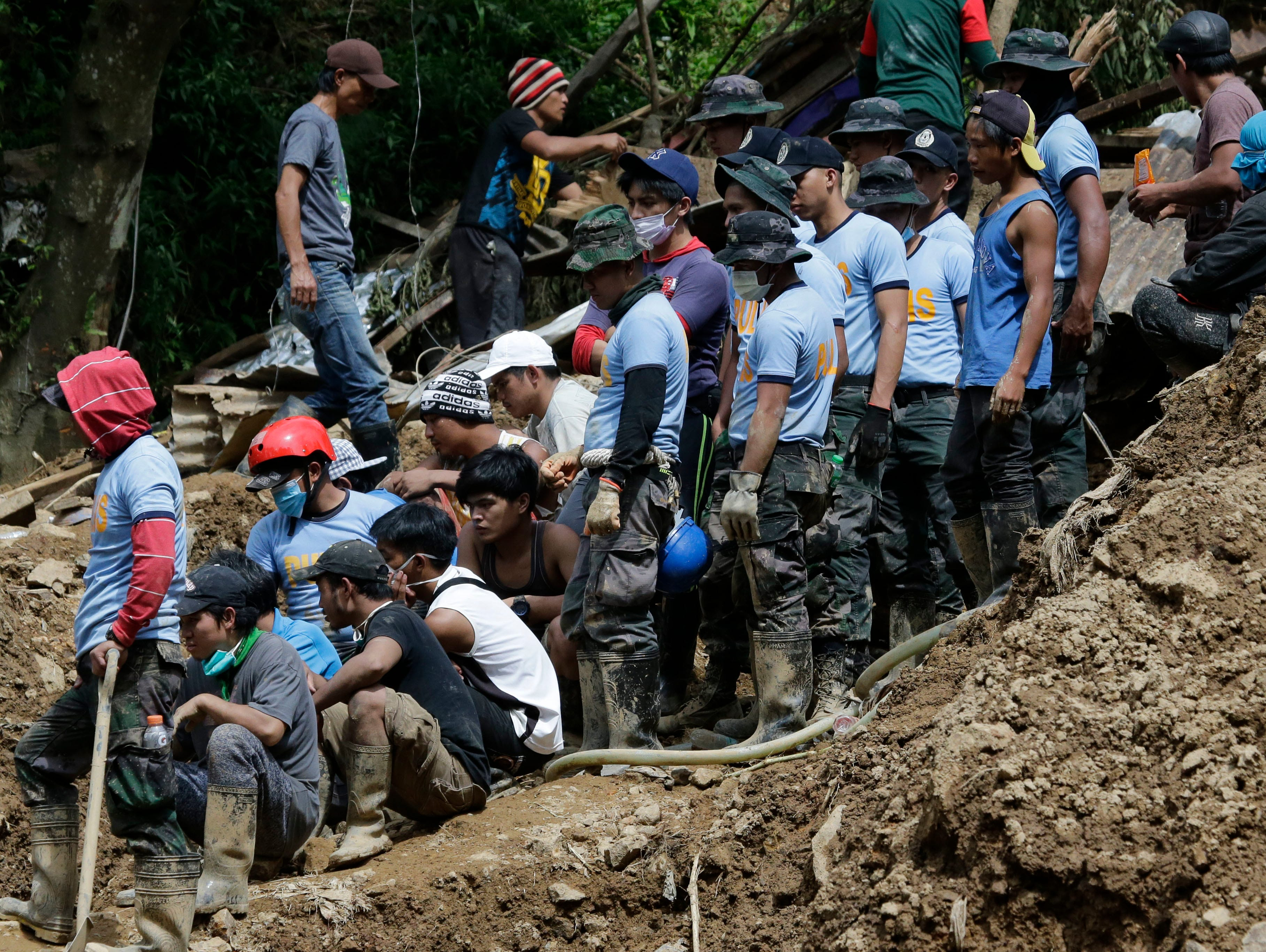Rescuers watch a body as its recovered where a landslide was set off by Typhoon Mangkhut as it lashed across Itogon, Benguet province, northern Philippines, Tuesday, Sept. 18, 2018. Dozens of people believed buried in the landslide probably did not survive, the mayor of Itogon said Monday, although rescuers kept digging through mud and debris covering a chapel where they had taken shelter.