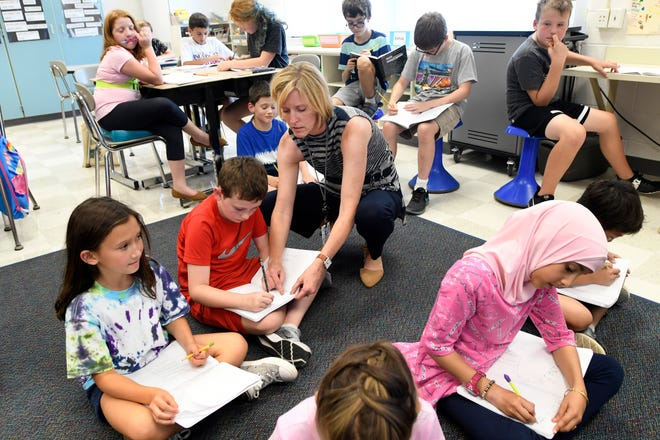 Fifth grader teacher Erin Wenrick, middle, helps her students with their reading, Monday, Sept. 17, 2018 at Tonda Elementary School in Canton, Michigan.