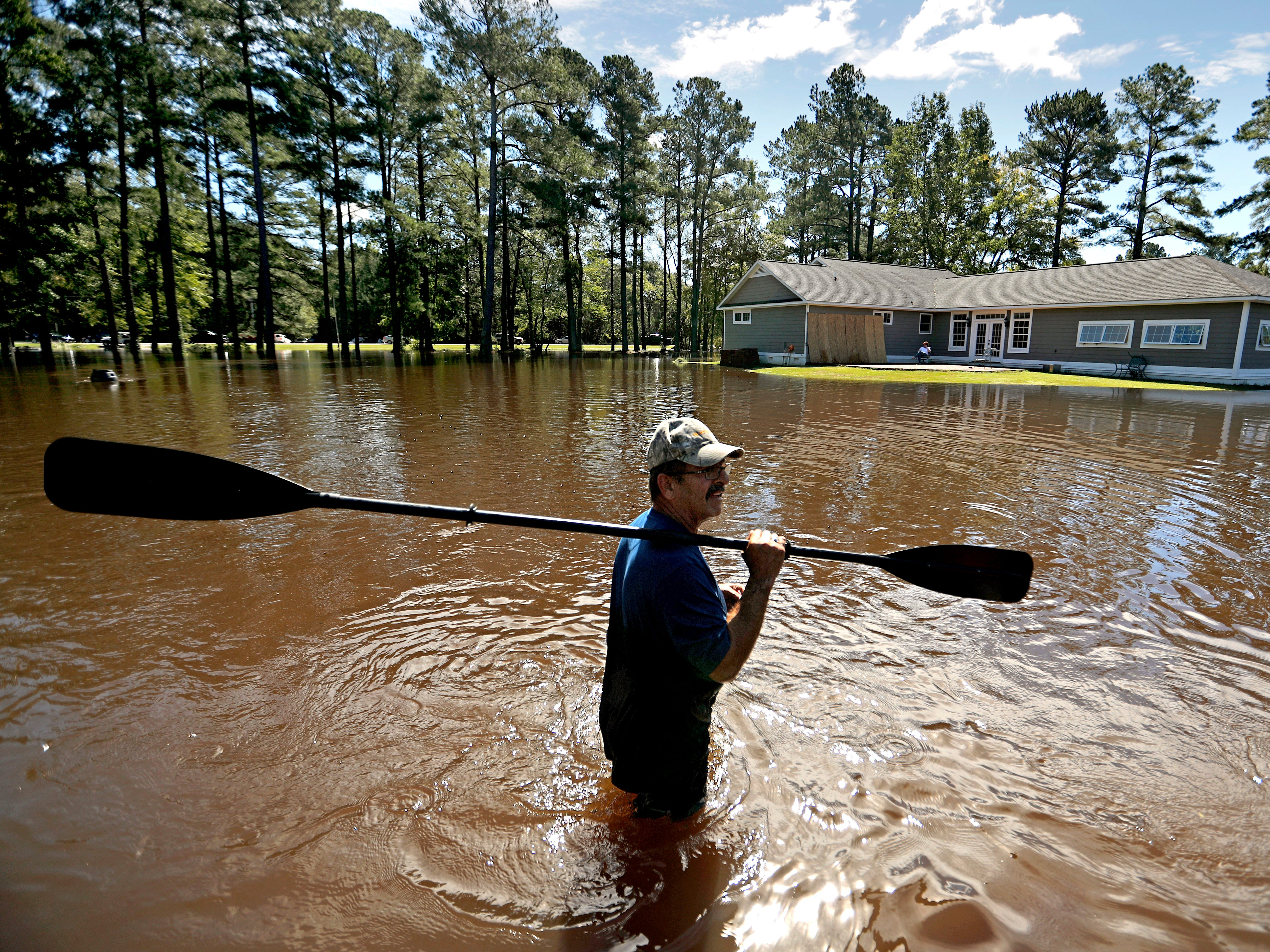 The home of Kenny Babb is surrounded by water as he retrieves a paddle that floated away while the Little River continues to rise in the aftermath of Hurricane Florence in Linden, N.C., Tuesday, Sept. 18, 2018.