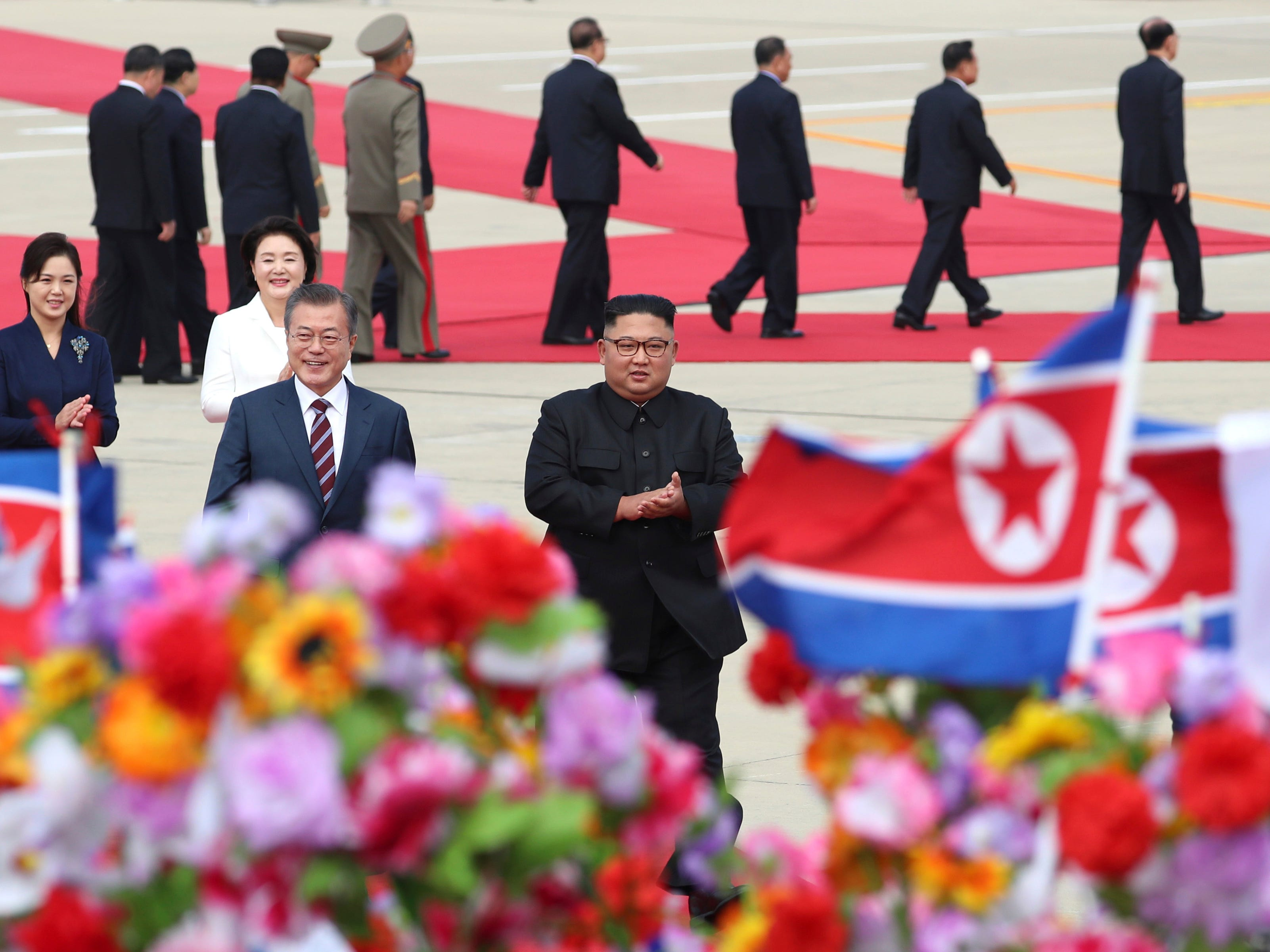 South Korean President Moon Jae-in, front left, walks with North Korean leader Kim Jong Un, front right, upon Moon's arrival at Sunan International Airport in Pyongyang, North Korea, Tuesday, Sept. 18, 2018.