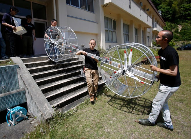 In this June 3, 2017, file photo, members of Cartivator carry propellers of the test model flying car in Toyota, central Japan.