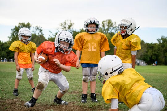 Broncos player Jack Lehman, 8, front left, rushes the ball past teammate Wyatt Fetscher, 7, front right, during a drill at an Evansville Junior Football League, practice held at Howell Park in Evansville, Ind., Tuesday evening, Sept. 11, 2018.