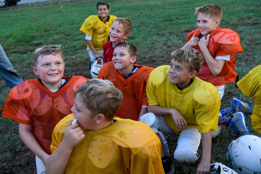 Members of the Broncos, a team of second and third graders in the Evansville Junior Football League, laugh at a knock-knock joke told during a team huddle at the end of practice at Howell Park in Evansville, Ind., Tuesday evening, Sept. 11, 2018.