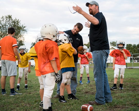 Broncos Head Coach Jake Boehman, right, talks to his team about running drills as Assistant Coach Kevin Folz, center right, gives Brady Beal, center left, advice during an Evansville Junior Football League practice held at Howell Park in Evansville, Ind., Tuesday evening, Sept. 11, 2018.
