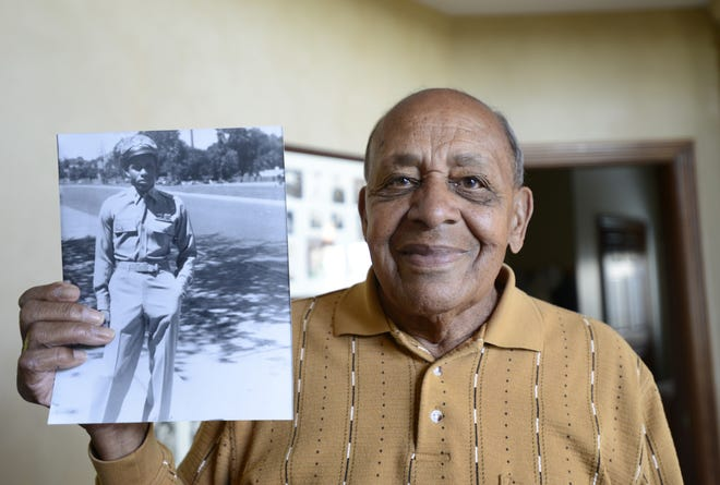 Harold Brown in this 2015 photo holds a picture of himself at 20 years old after returning home from World War II. Brown and six other living Tuskegee Airmen/pilots will be honored at the American Veterans Center in Washington on October 26-27.
