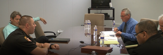 Brandon Kimmet, near left, is questioned by Lucas County Sheriff's Office Internal Affairs members, right, about whether he deleted items from a county-owned computer.