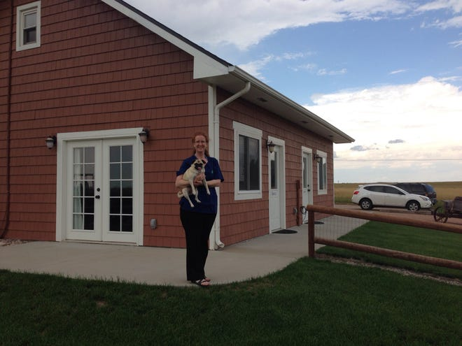Dr. Kathleen Cooney stands outside Guardian Pet Aquamation in Loveland with her pug, Darby.