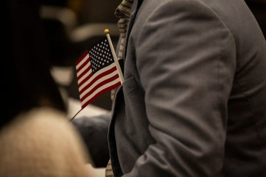 A cloth Start Spangled Banner sticks out of Carlos Sanchez's suit at the be dinging of Naturalization Oath Ceremony at the U.S. Citizenship and Immigration Services, Fort Myers office on the morning Tuesday Sept. 18, 2018.