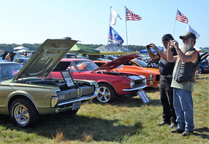 Two gentlemen from Green Bay, who identified themselves as only Snake and Dave, photograph a vehicle at the Oconto Fly-in, Car & Tractor Show on Sept. 15 at the Oconto-J. Douglas Bake Municipal Airport.