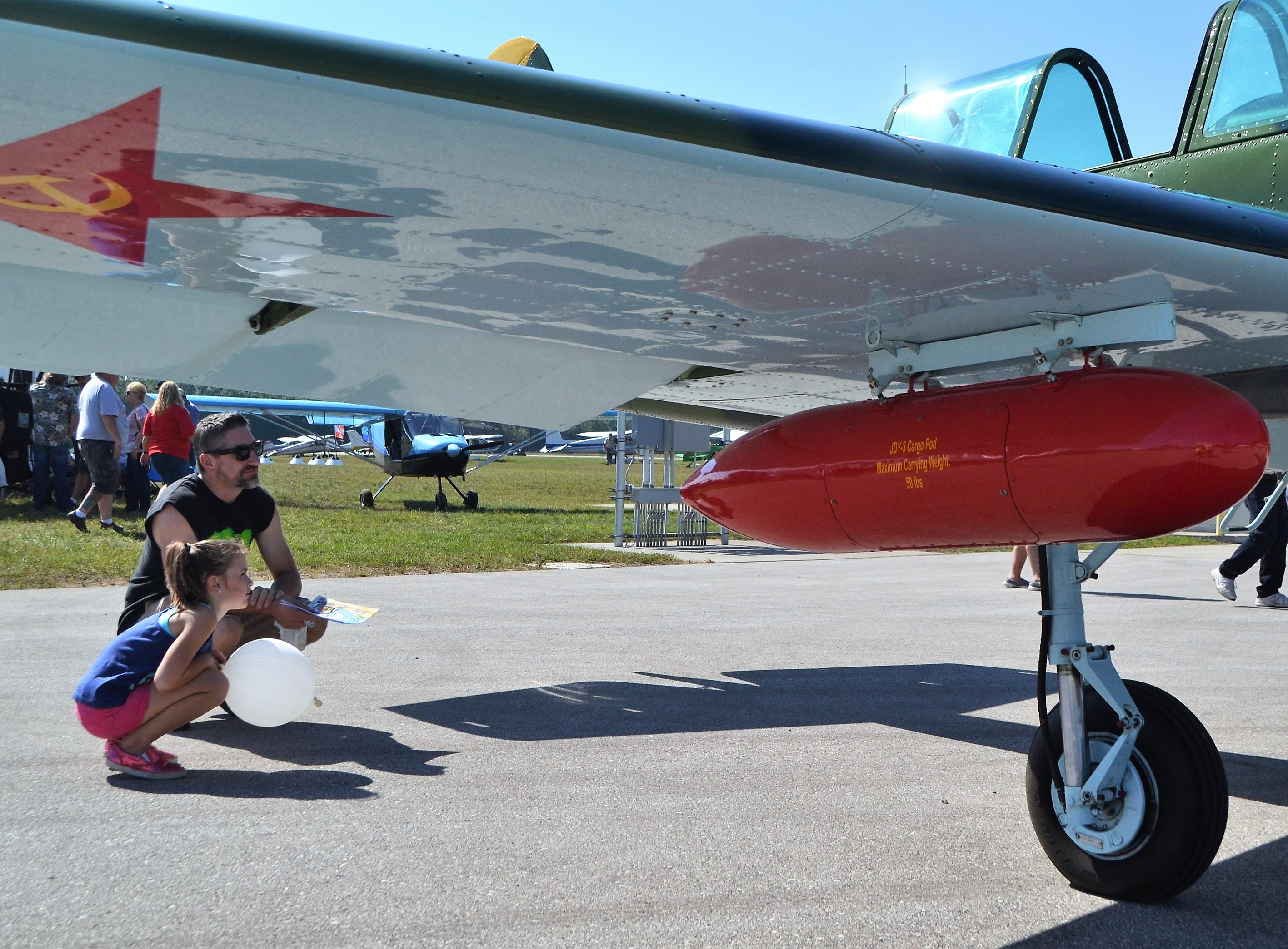 Rob Hansen of Oconto and his daughter, Ruby, 7, look over the YAK, flown in the '40s by the Soviet Union, at the Oconto Fly-in, Car & Tractor Show on Sept. 15 at the Oconto-J. Douglas Bake Municipal Airport.