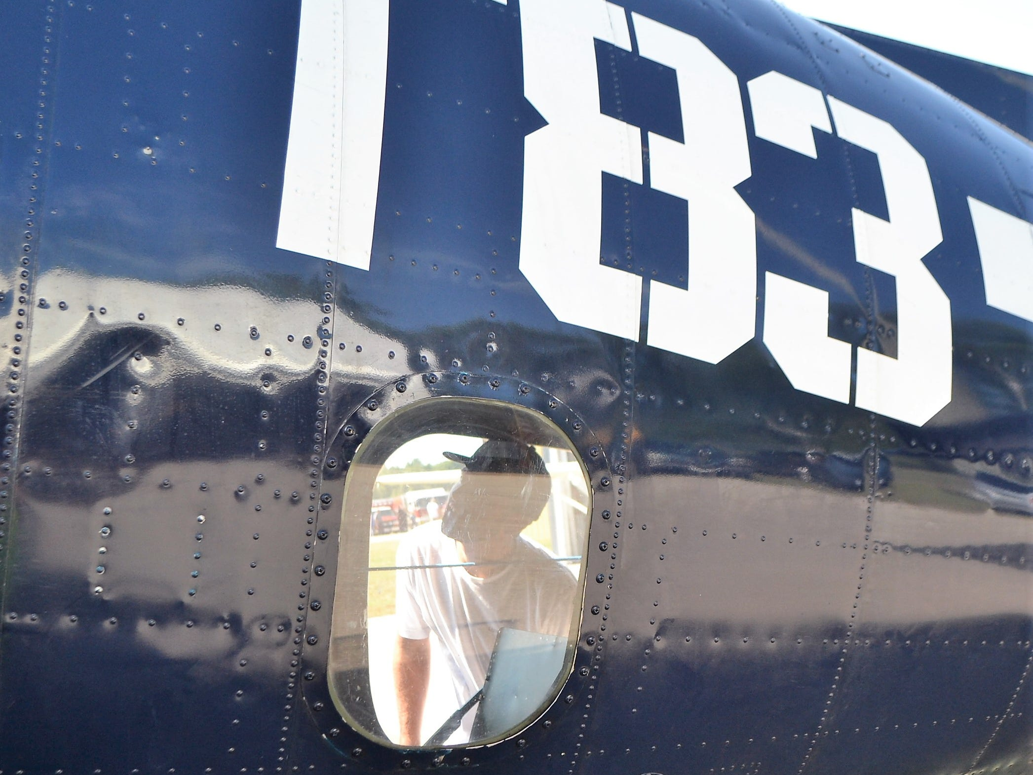 Connor Roscoe of Connecticut is seen through a window looking at the interior of the TBM Avenger at the Oconto Fly-in, Car & Tractor Show on Sept. 15 at the Oconto-J. Douglas Bake Municipal Airport. Roscoe and a friend were traveling cross-country and heard about the show and decided to stop by.