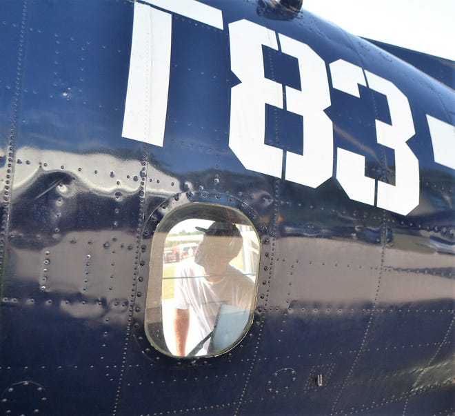 Connor Roscoe of Connecticut is seen through a window looking at the interior of a TBM Avenger at the Oconto Fly-in, Car & Tractor Show in 2018 at the Oconto J. Douglas Bake Municipal Airport. Roscoe and a friend were traveling cross-country and heard about the show and decided to stop by.