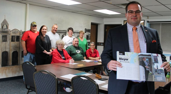 "Before beginning a meeting last month, Gillett Mayor James Beaton displays the ""American Funeral Director"" profile written about his dual role as mayor and funeral director. With Beaton are city officials, front row from left, Nanette Mohr, Matthew Stroik, Irene Drake; and back row, Shane Rank, Chelsea Henkel, Ron Anderson, Marie Blaser, and Sandy Hubbard."