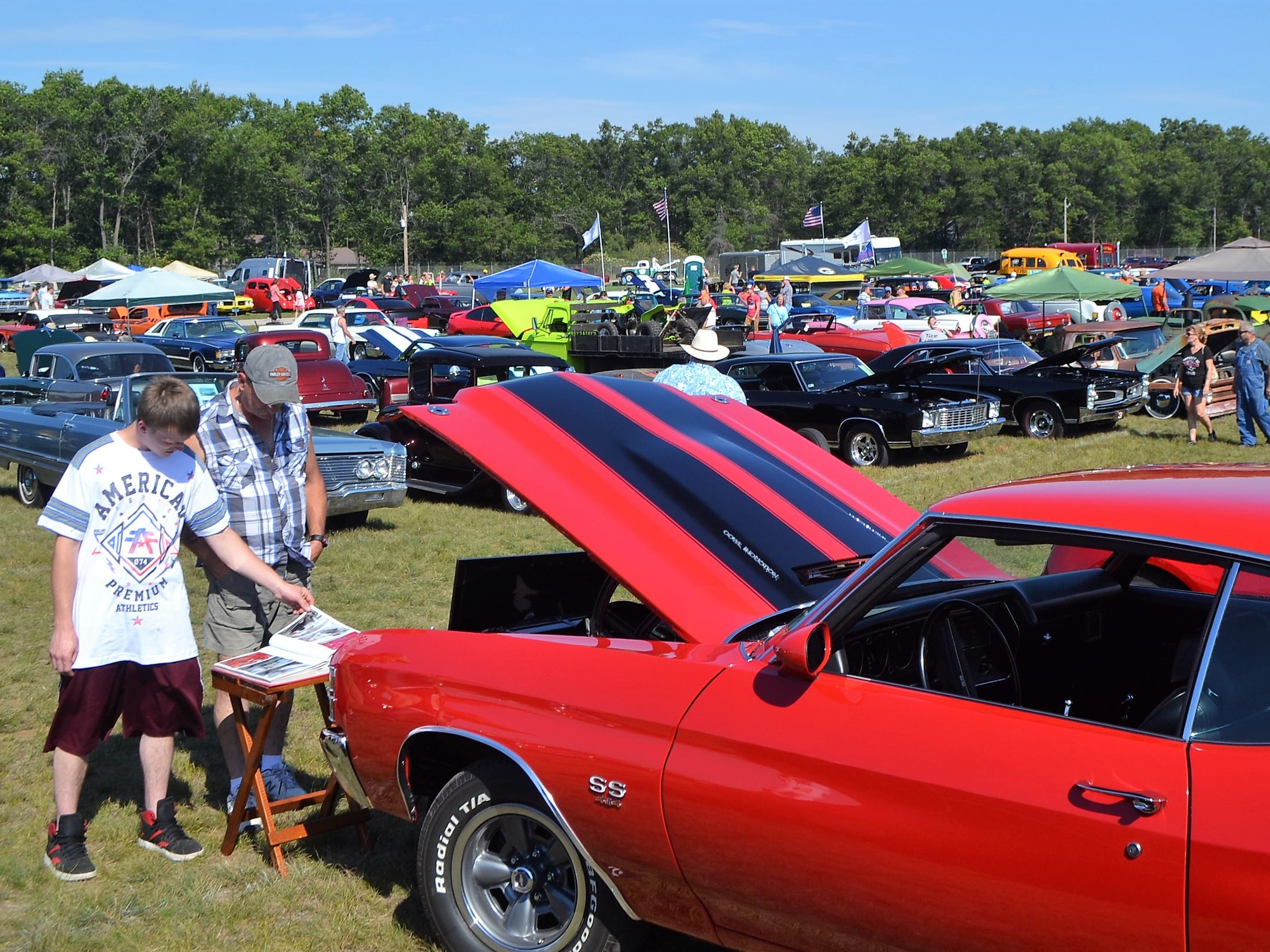 Jeff and John Hanna look over the booklet of information on the 1971 Chevelle at the Oconto Fly-in, Car & Tractor Show on Sept. 15 at the Oconto-J. Douglas Bake Municipal Airport. Nearly 300 cars were exhibited.