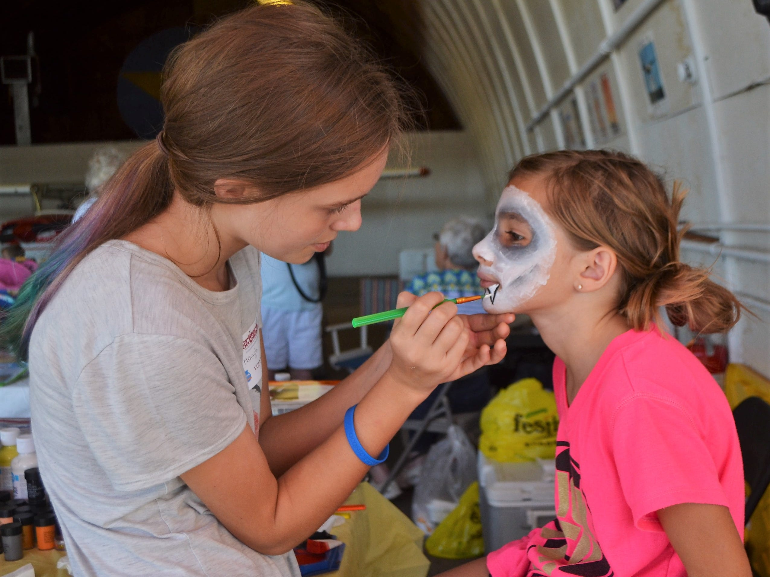 Mikhayla Steele of Oconto paints a vampire face onto Alia Comins, 8, of Lena at the Critter Companions booth at the Oconto Fly-in, Car & Tractor Show on Sept. 15 at the Oconto-J. Douglas Bake Municipal Airport.