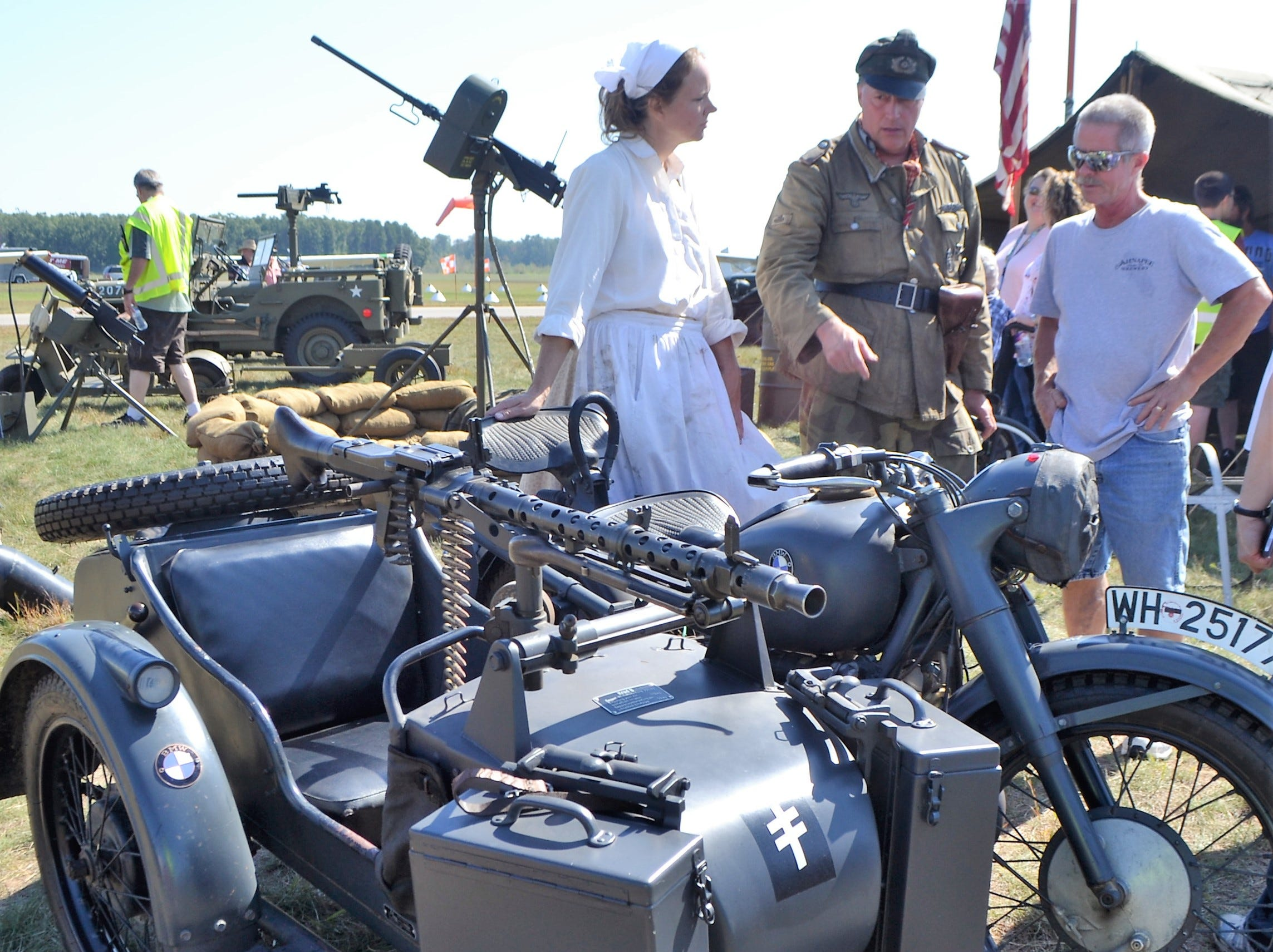 Jeff Ellinger, center, explains his 1939 BMW motorcycle, used by the German Army in WWII, to Scott Kaufman of Pulaski at the Oconto Fly-in, Car & Tractor Show on Sept. 15 at the Oconto-J. Douglas Bake Municipal Airport. Ellinger is wearing the uniform of the German soldier in the Panzer division 3rd Unit, while his wife is dressed as a German peasant. The gun mounted on the sidecar is an 8mm machine pistol.