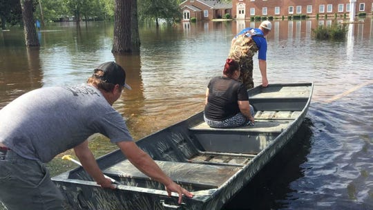 Jess White (left) and Allen Anderson guide Sarah Brown back to her now-flooded home using a boat in the Long Avenue neighborhood of Conway on Monday, September 17, 2018. A nearby swamp has flooded, bringing water into the neighborhood in the aftermath of Hurricane Florence.