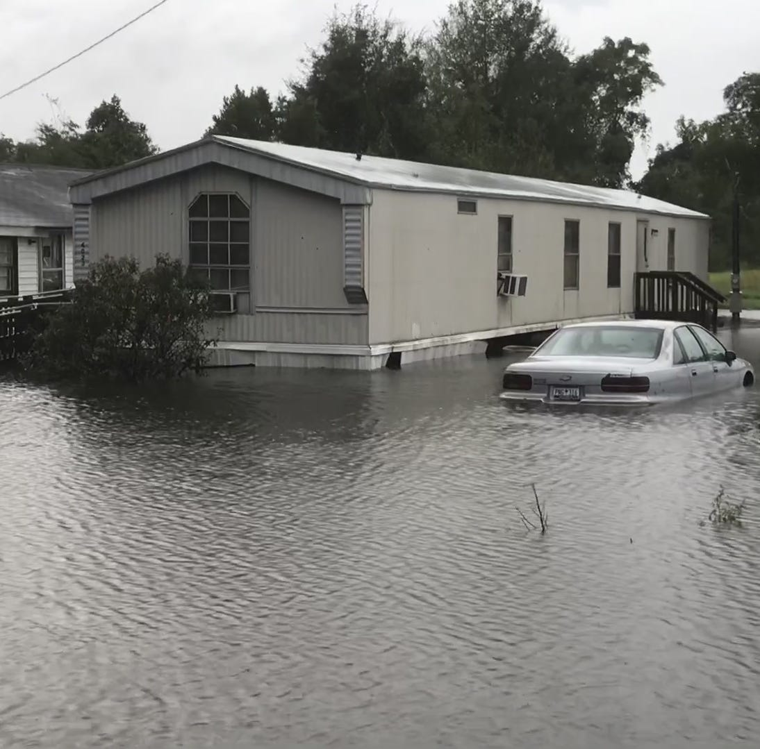 A car next to a mobile home is partially submerged by floodwaters south of Mullins.