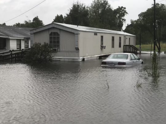A car next to a mobile home is partially submerged by floodwaters along State 41 south of Mullins.