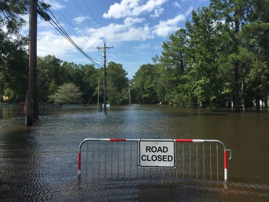 """A """"road closed"""" sign marks a flooded street in the Long Avenue neighborhood of Conway on Monday, Sept. 17, 2018."""