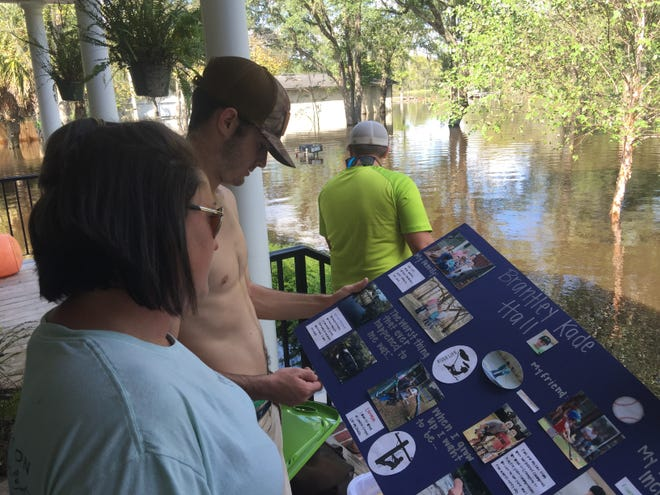 "Whitney Hall and her son Mackenly Hucks examine a school project made by Hall's younger son before placing it in their boat Tuesday, Sept. 18, 2018 on Pitch Landing Drive in Conway, while floodwaters from Hurricane Florence rise around her home. A panel on the poster board reads, ""The worst thing that ever happened to me was... Hurricane Matthew."""