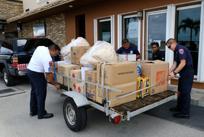From left, Guam Fire Department acting Chief Joey San Nicolas, firefighter Richard Cotelesse, Wyndam Garden Guam maintenance leader Joe Sigrah and GFD spokesman and firefighter Kevin Reilly secure donations for Rota relief outside  Wyndam Garden Guam in Tamuning on Sept. 17, 2018.  Wyndham, Days Inn Guam and Grand Plaza Hotel donated emergency supplies for Rota residents in the wake of Typhoon Mangkhut, which directly hit Rota on Sept. 10, 2018. The hotels decided to take action when they learned of a drive for Rota coordinated by GFD and the Western Pacific Association of Fire Chiefs. Items purchased by the hotels included 30 portable gas cookers, 280 butane cans, 16 cases of assorted paper products, 10 machetes, 13 flashlights, 180 batteries, 100 trash bags and 240 cans of Spam. In addition, 50 gently used blankets and 48 food and other items were donated by hotel employees. The U.S. Coast Guard offered to help get the supplies to Rota, according to Reilly.
