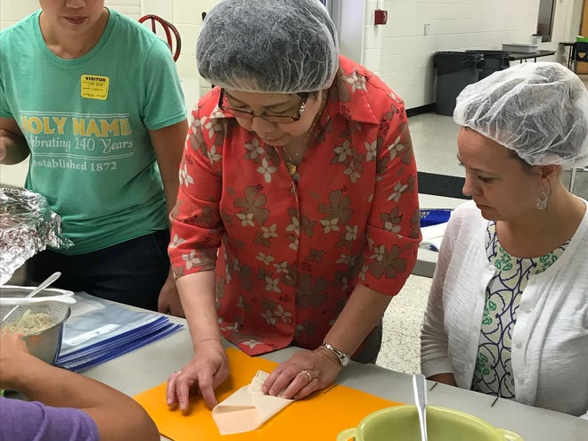 Sandy Berger (left), Eve Tiu (center), and Terre Hurtte (right) work in the Holy Name School cafeteria to assemble and roll hundreds of eggrolls.