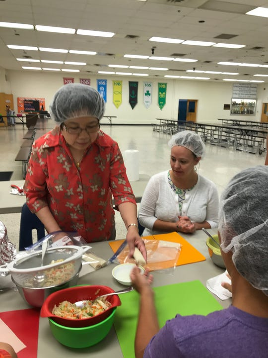 Eve Tiu teaches volunteers the proper size of an eggroll.