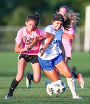 Noblesville's Keely Hoopingarner (26) and Carmel's Elizabeth Hargis (7) battle for the ball at White River Elementary School soccer complex on Monday, Sept. 17, 2018.