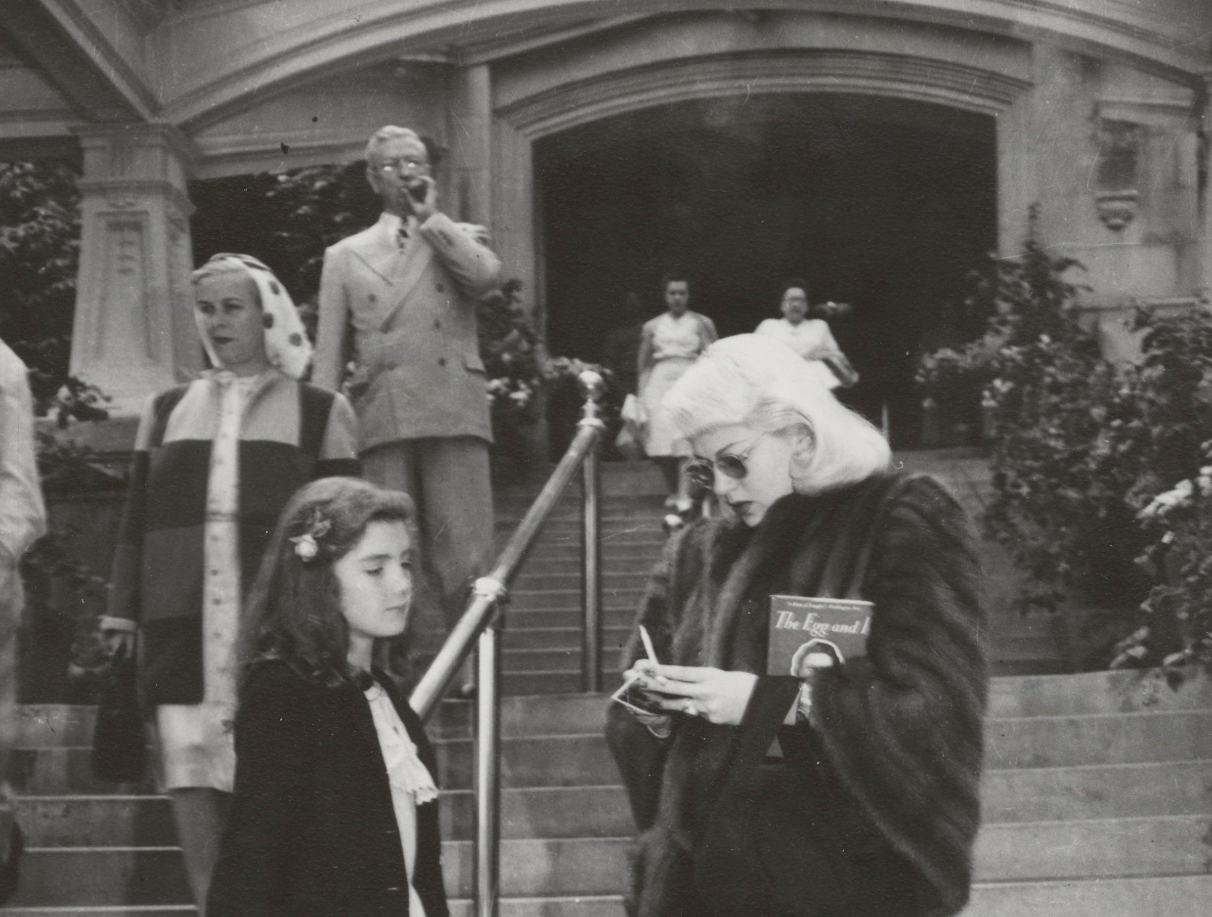 Actress Lana Turner gives an autograph to a young girl at the entrance to the French Lick Springs Hotel in 1945.