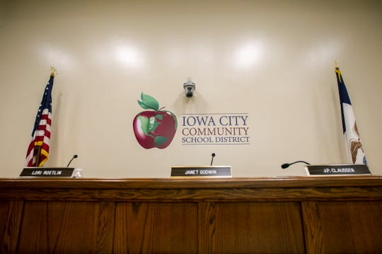 A school district logo is seen behind member seats on Tuesday, Sept. 18, 2018, at the Iowa City Community School District offices in Iowa City.