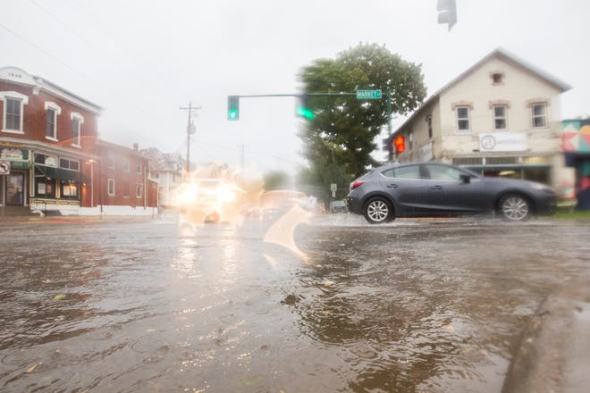 Vehicles drive through flash flooding on Tuesday morning, Sept. 18, 2018, on the corner of Market and Gilbert Streets in Iowa City.