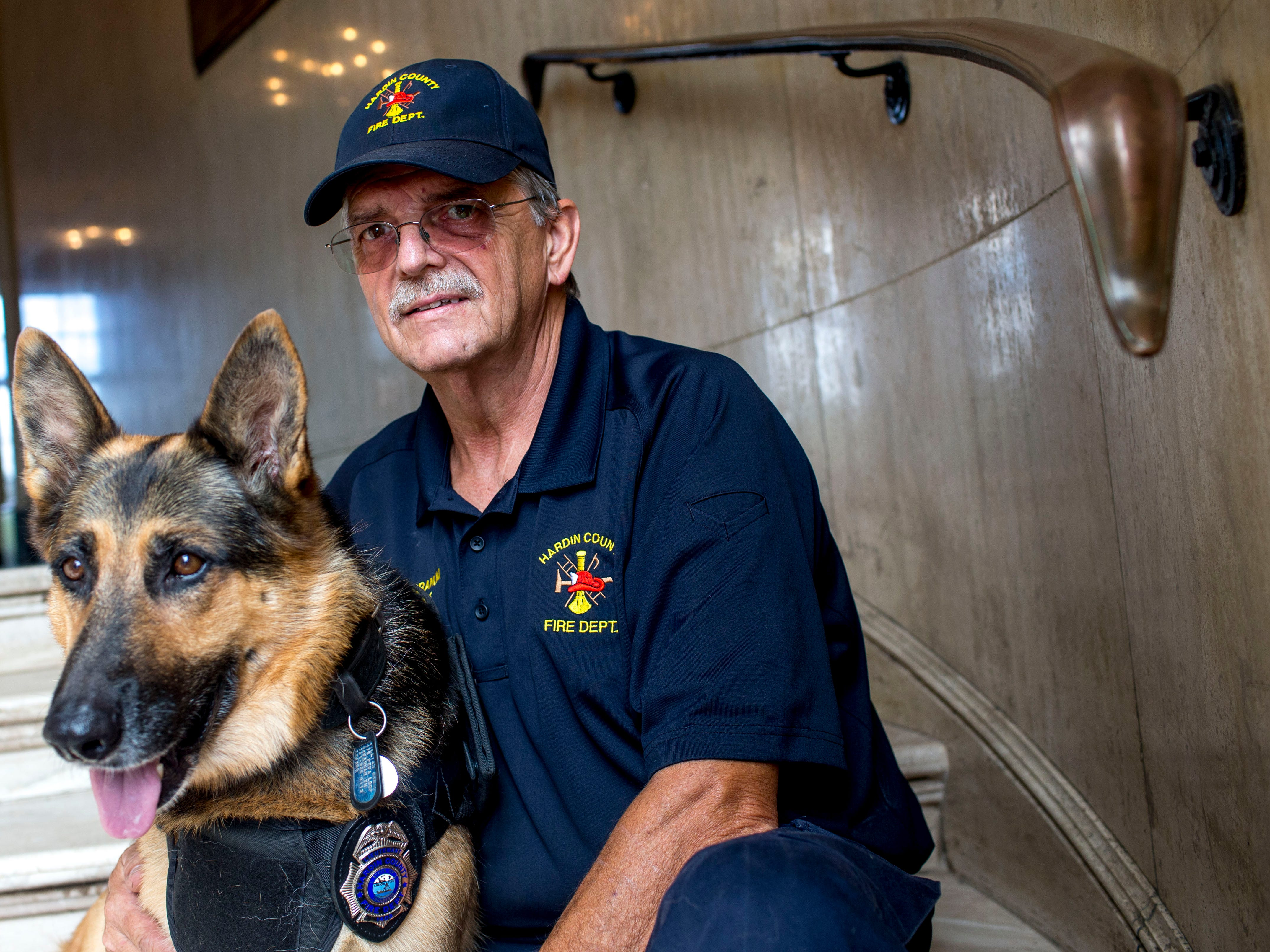 William Branum, the Hardin County fire district 14 chief, right, and his partner Jodi-Le, a German shepherd, are both cancer survivors and made it through their ordeals while working with one another for the County, sit on the steps at Hardin County Circuit Court in Savannah, Tenn., on Monday, Sept. 17, 2018.