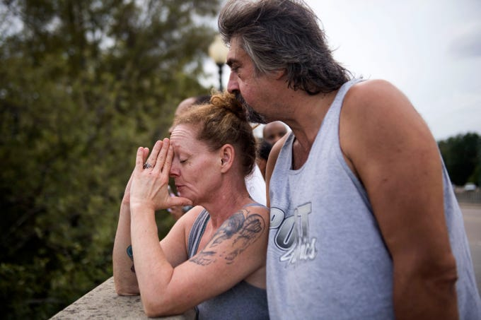 D.J. Grimsley of Fayetteville kisses his wife Sabrina on the head as she prays for victims of the flood, while looking toward the rising Cape Fear River on Person Street Bridge in Fayetteville, N.C., Monday, Sept. 17, 2018. The flood stage for the Cape Fear River is 35 feet, and after Florence the river stands at over 50 feet. It is predicted to peak at 61.8 feet according to the National Weather Service.