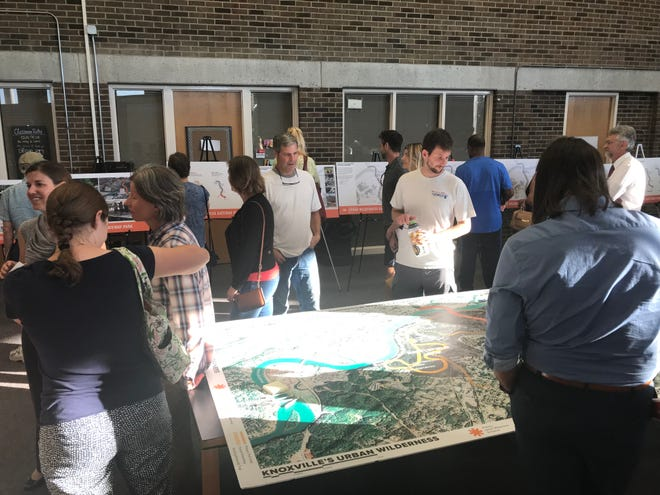 Residents look over large maps and scaled drawings of plans for the city's Urban Wilderness Gateway Park at South Doyle Middle School Tuesday, September 2018.