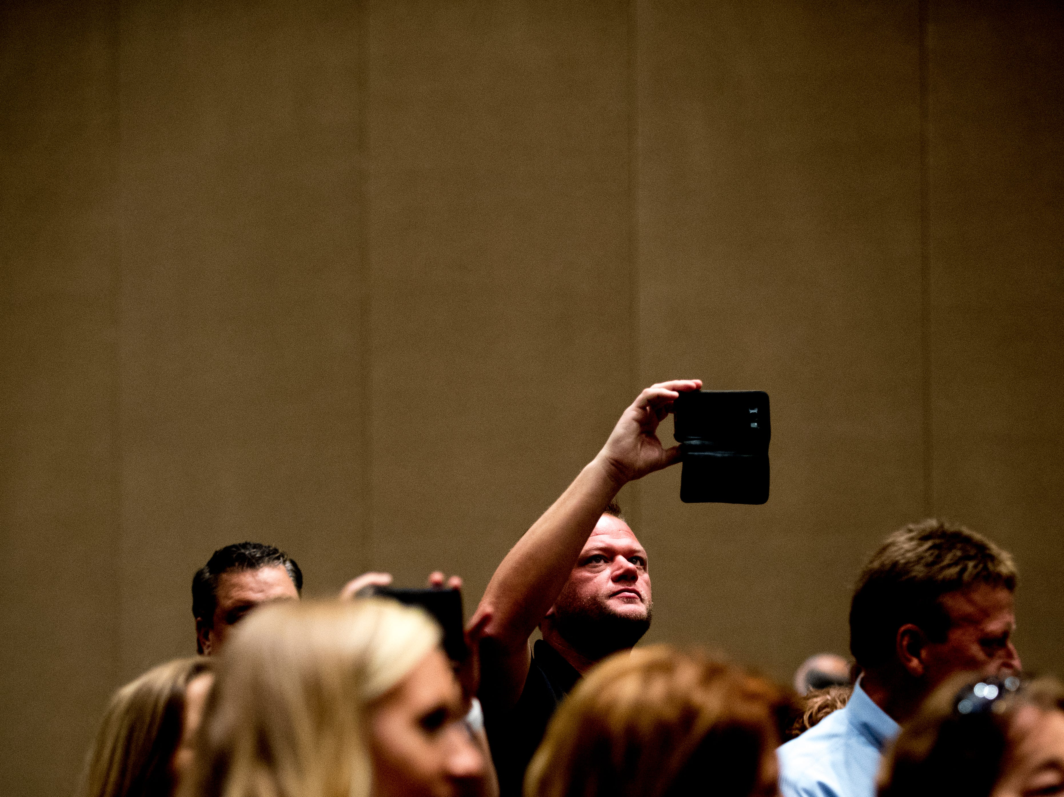 An attendee snaps a photo from the back of the room during an announcement ceremony for Ole Red Gatlinburg in Gatlinburg, Tennessee on Tuesday, September 18, 2018. The 13,500 square-foot entertainment venue with a two-story bar, restaurant and performance space with space for 325 patrons is slated to open spring 2019.