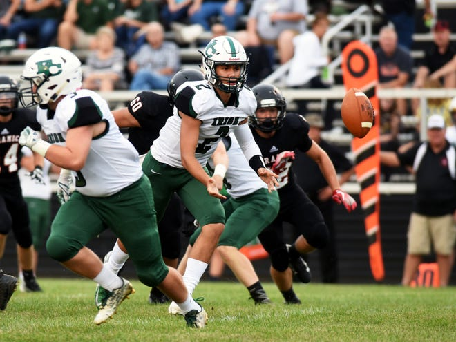 Fisher Catholic quarterback Kaden Starcher pitches the ball to a teammate in the first quarter against Crooksville.