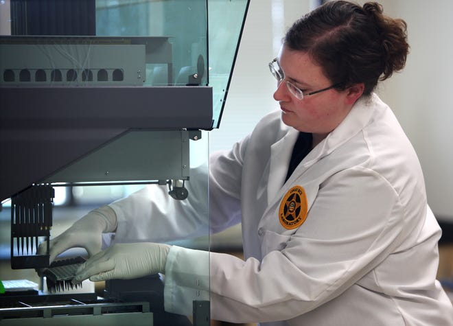 Sarah Glass, a scientist in the DNA Unit at the Bureau of Criminal Investigation in London, Ohio, works with a robot that allows them to profile 80 samples at a time in this January 2000 file photo.