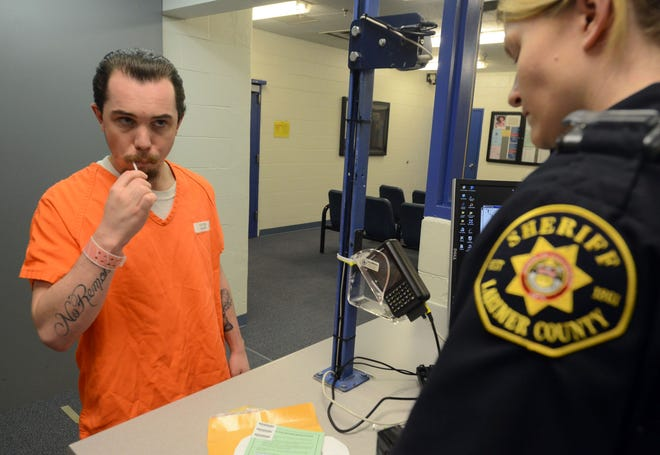 In this 2013 file photo, a prisoner in the Larimer County Jail demonstrates how he moved a DNA swab in his mouth after being arrested. Under Ohio law, prisoners in jail on qualified charges must submit a DNA sample that will be compared to other samples in a crime database.
