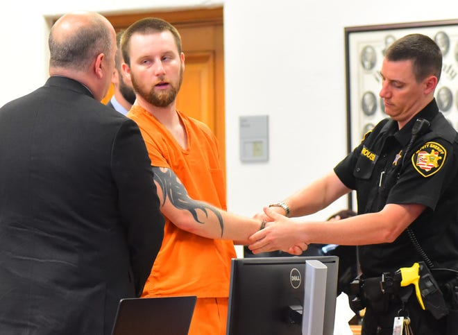Shawn Lawson, center, talks to his attorney Anderson Sanderson, left, as Lawson is handcuffed by and Athens County Sheriff's deputy after being sentenced to 40 years in prison in Athens County Common Pleas Court. Lawson was sentenced to prison after being charged with three rapes and one attempted rape.