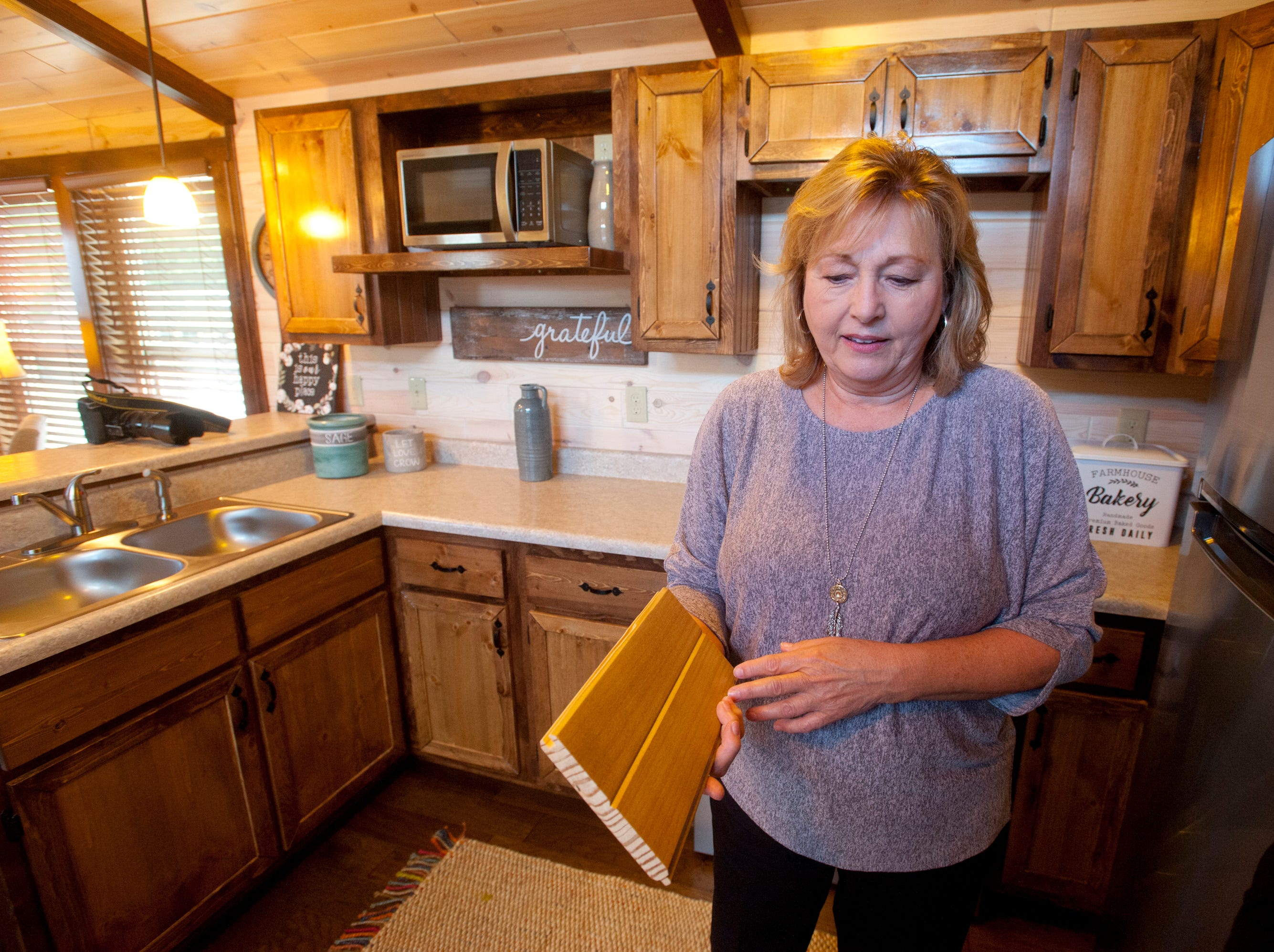 """Amish Made Cabins of Shepherdsville is making this """"White River"""" cottage, geared toward its elderly and disabled customers. Here, co-owner Pamela White shows a piece of the white pine tongue and groove used in the kitchen's backsplash. The wood was finished at the manufacturer with a white wash.September 10, 2018"""