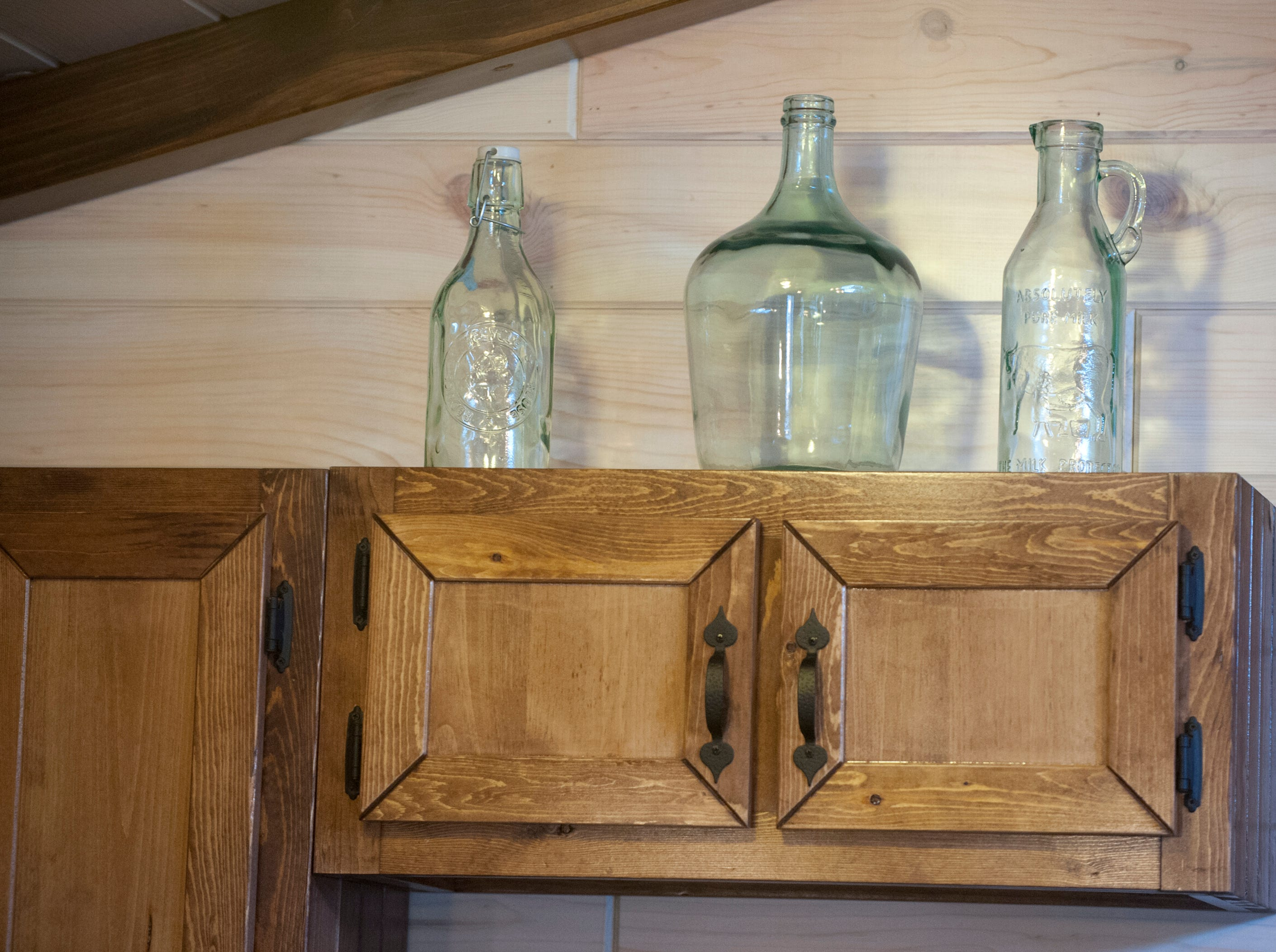 Glass bottles decorate the top of the kitchen cabinets.