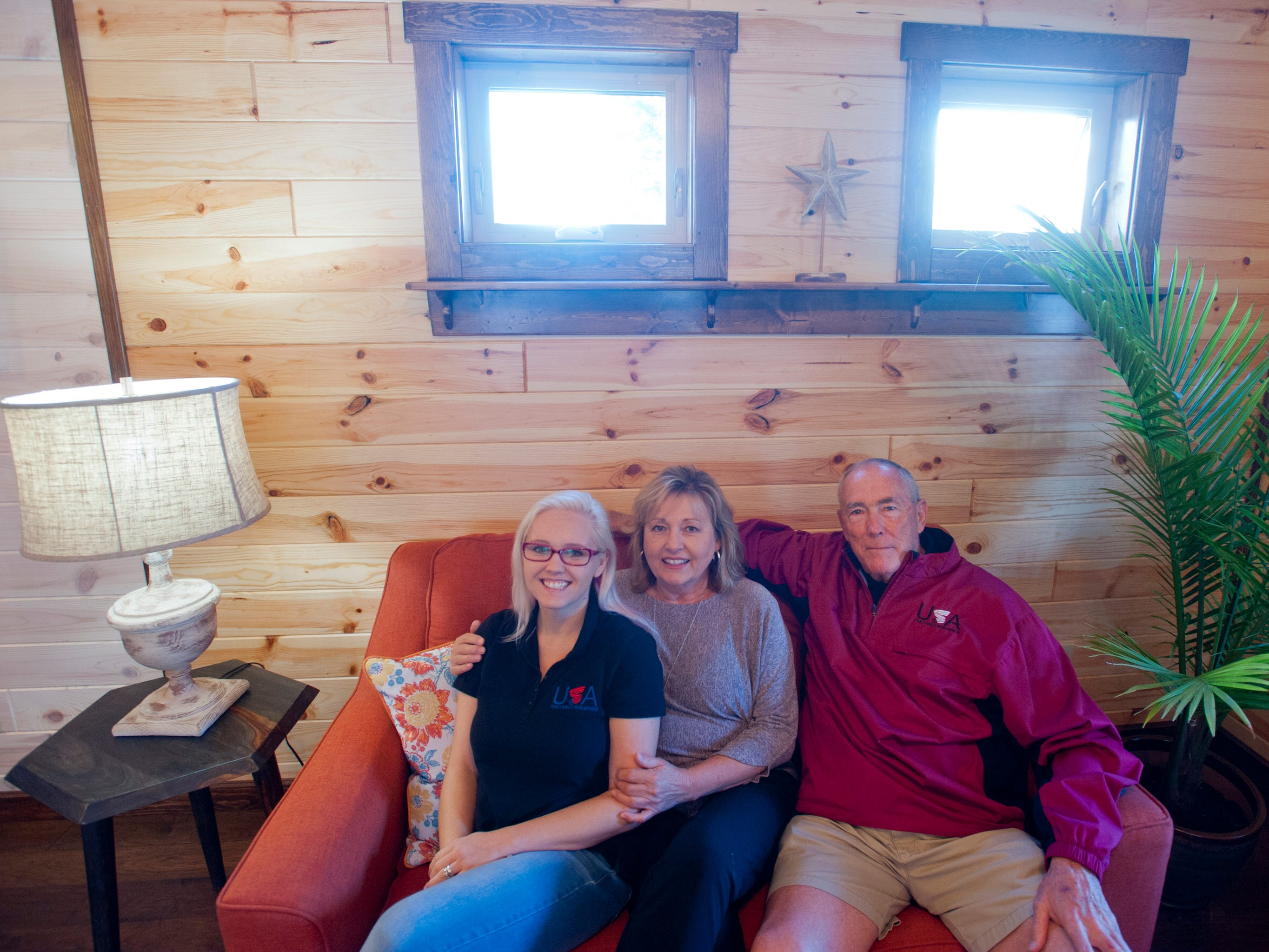 """Amish Made Cabins of Shepherdsville is making this """"White River"""" cottage, geared toward its elderly and disabled customers. Here, owners Pamela and Jim White relax in the home's front living room with their daughter-in-law, Jennifer, left.September 10, 2018"""